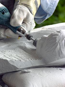 marble sculptor using a handheld grinder