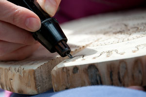 carver using a wood burning tool